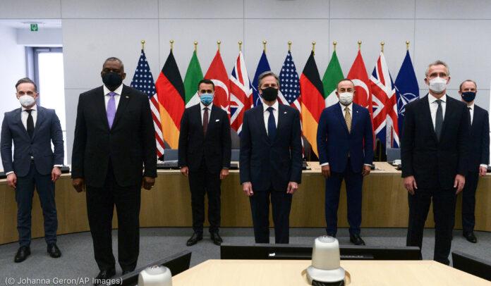 Sept hommes debout avec beaucoup de drapeaux à l'arrière-plan (© Johanna Geron/AP Images)