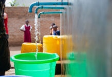 Bucket and water container filling from outdoor spigots as schoolchildren look on (© Water for People)