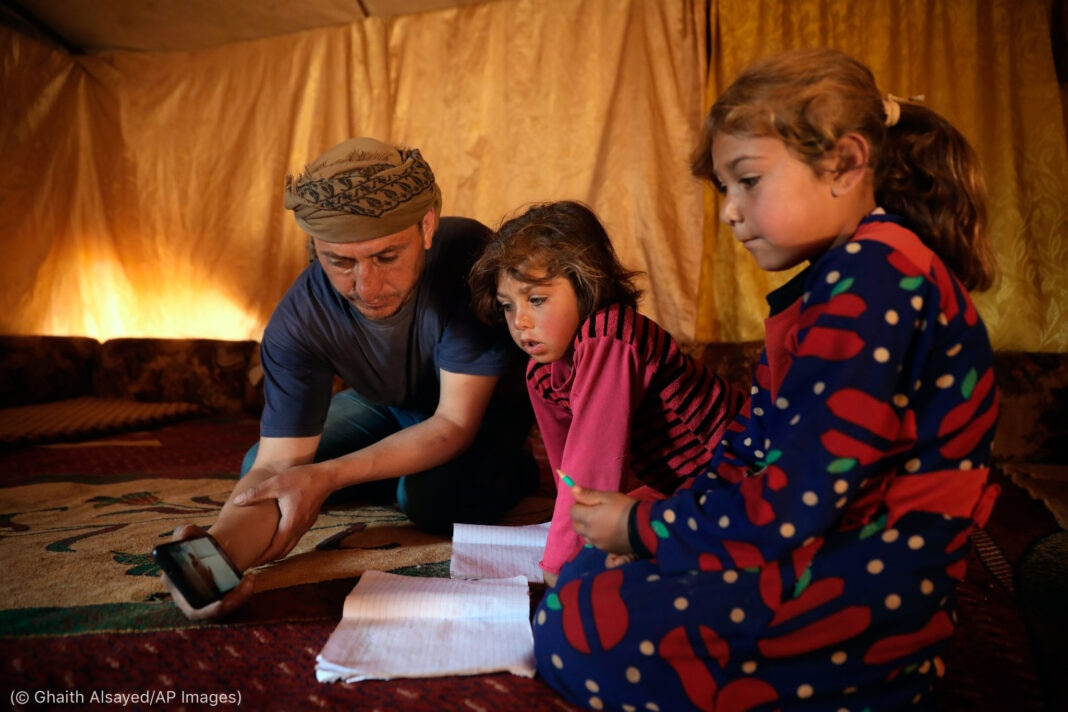 Man tutoring his two young daughters in a tent (© Ghaith Alsayed/AP Images)