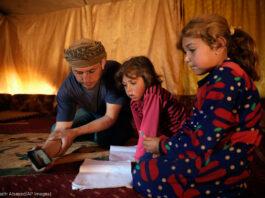 Un hombre sentado en el suelo de una tienda de campaña sosteniendo un teléfono móvil mientras dos niñas miran (© Ghaith Alsayed/AP Images)