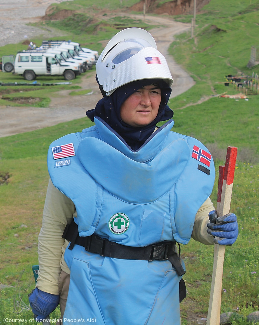 Woman wearing personal protective equipment in field (Courtesy of Norwegian People's Aid)