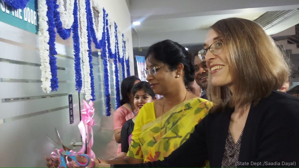 Women smiling and cutting ribbon in front of door (State Dept./Saadia Dayal)