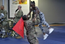 U.S. soldier holding a girl in the air during a celebration (U.S. Army/Staff Sergeant Paige Behringer)