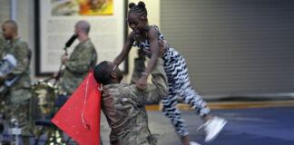 Un soldado estadounidense levanta a una niña en el aire durante una celebración (U.S. Army/sargento Paige Behringer)