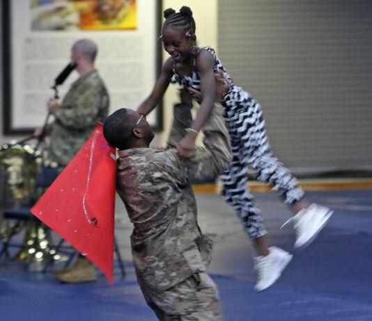 خوشی کا اظہار کرتے ہوئے ایک امریکی فوجی ایک بچی کو ہوا میں اچھال رہا ہے (U.S. Army/Staff Sergeant Paige Behringer)