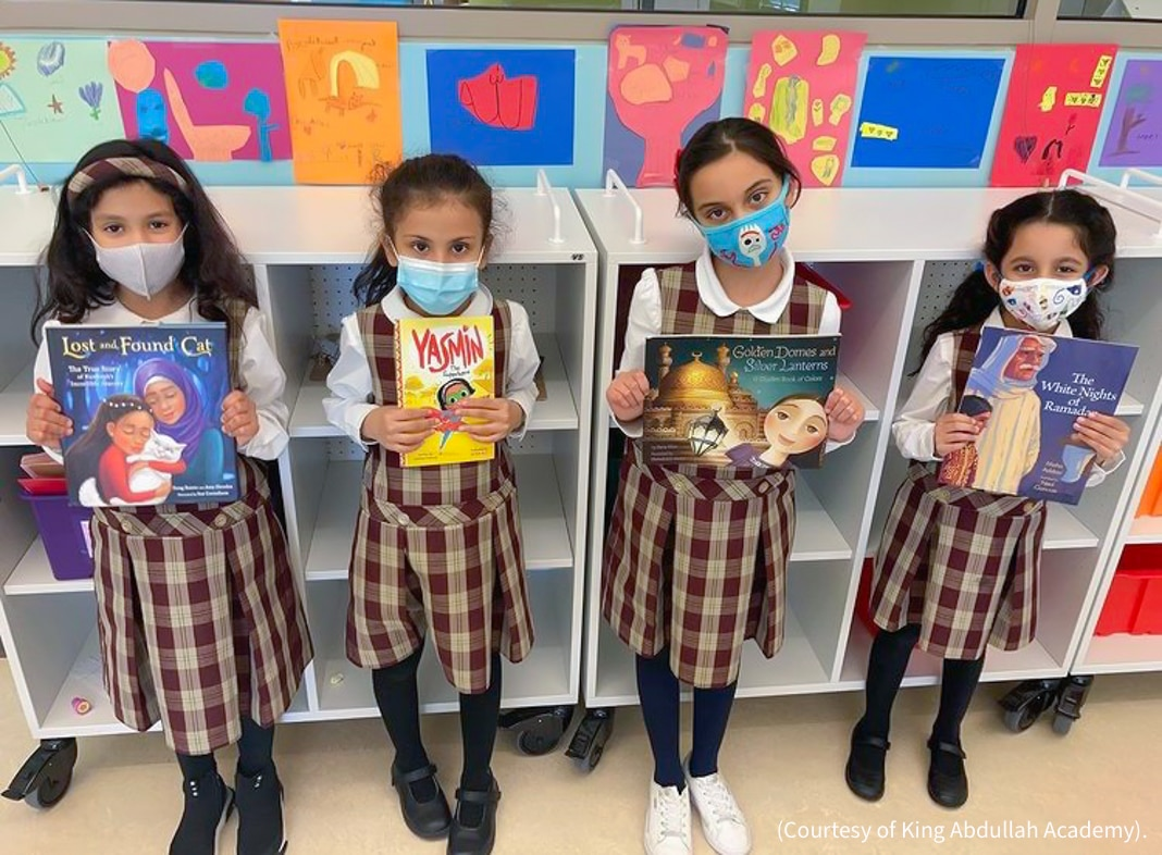 Four girls holding books (Courtesy of King Abdullah Academy)