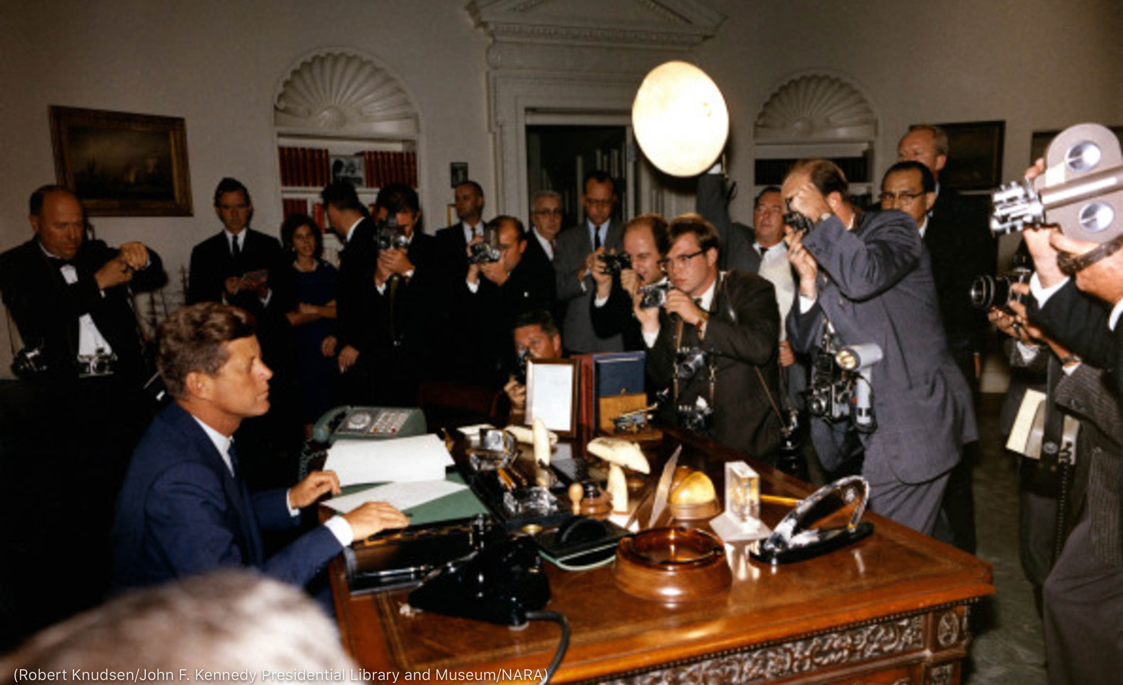 People holding cameras surrounding President Kennedy's desk (Robert Knudsen/John F. Kennedy Presidential Library and Museum/NARA)
