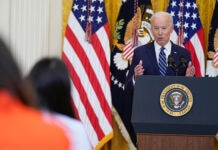 President Biden standing behind a lectern giving a press conference (© Evan Vucci/AP Images)