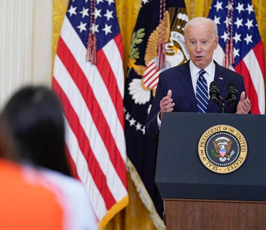 Le président Biden debout à un pupitre lors d'une conférence de presse (© Evan Vucci/AP Images)