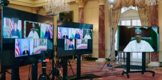Three large screens set up in elaborate hall containing screen views of leaders at virtual meeting (© Leah Millis/AP Images)
