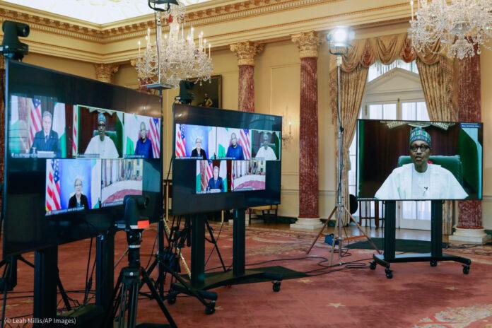 Three large screens set up in elaborate hall containing screen views of leaders at virtual meeting (© Leah Millis/AP Images)