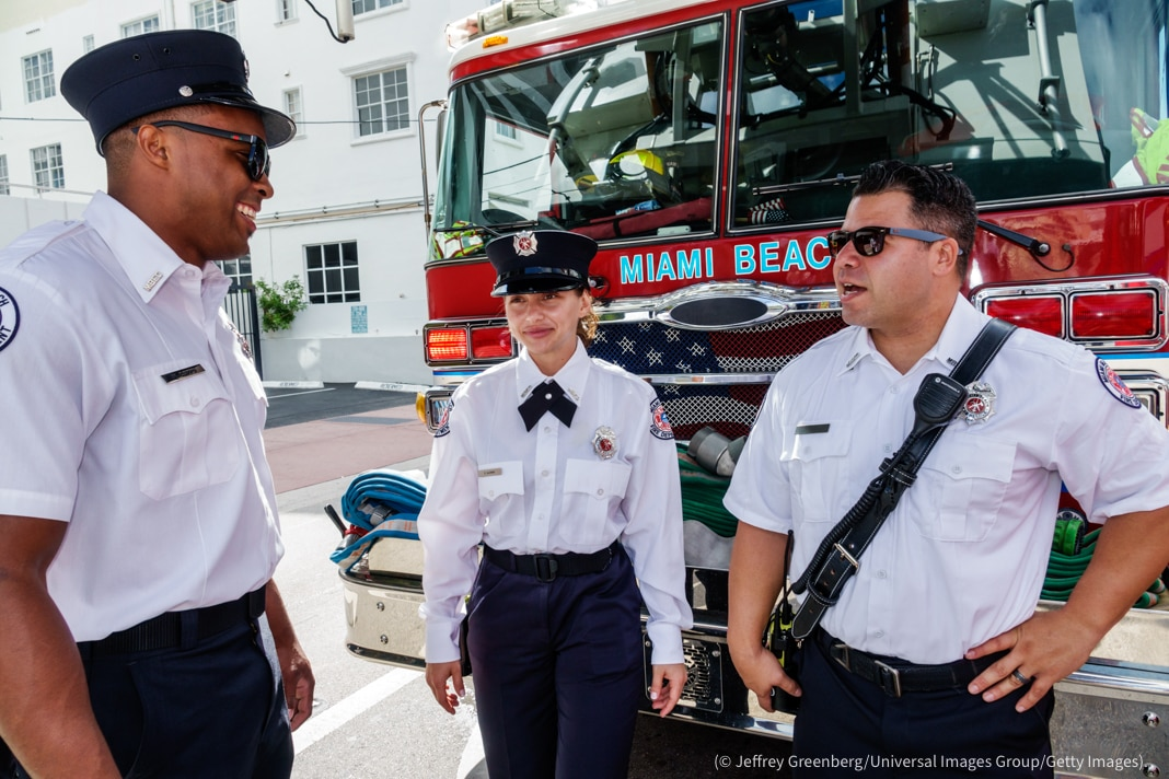 Three firefighters in uniform standing in front of fire truck (© Jeffrey Greenberg/Universal Images Group/Getty Images)