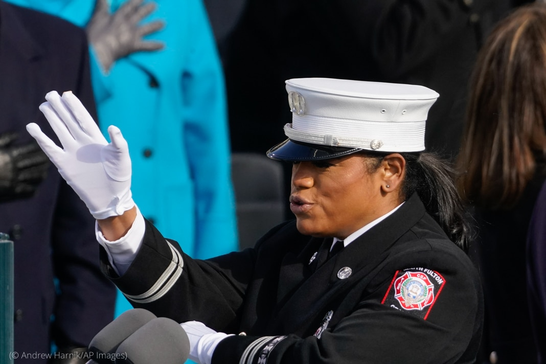 Woman wearing uniform raises her arm (© Andrew Harnik/AP Images)