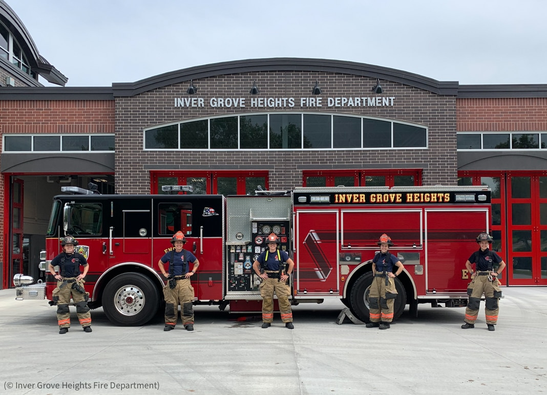 Five women wearing firefighting gear posing for photo in front of fire truck (© Inver Grove Heights Fire Department)