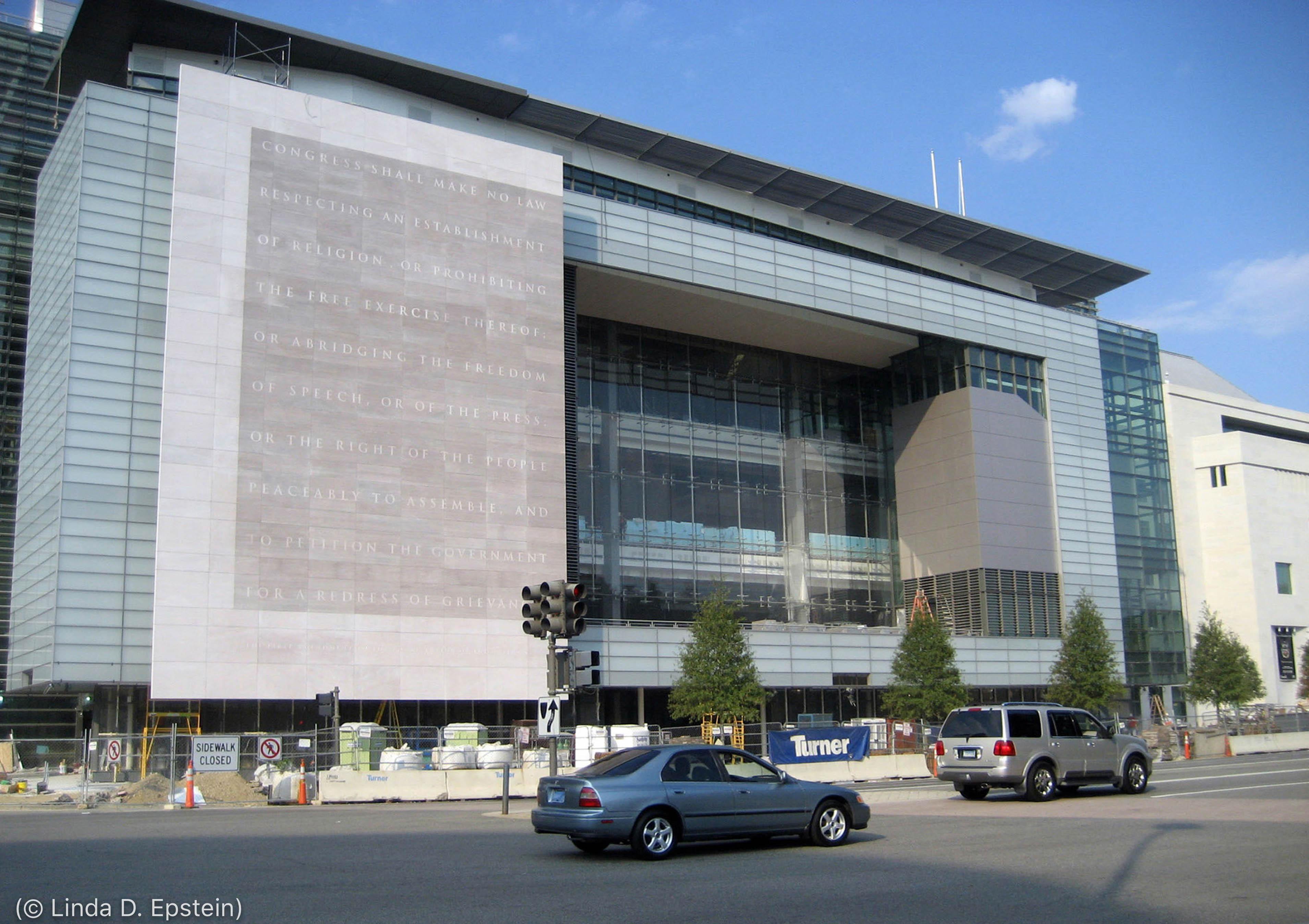 Fachada do antigo prédio do Newseum em Washington, com calçada bloqueada e carros passando (© Linda D. Epstein)
