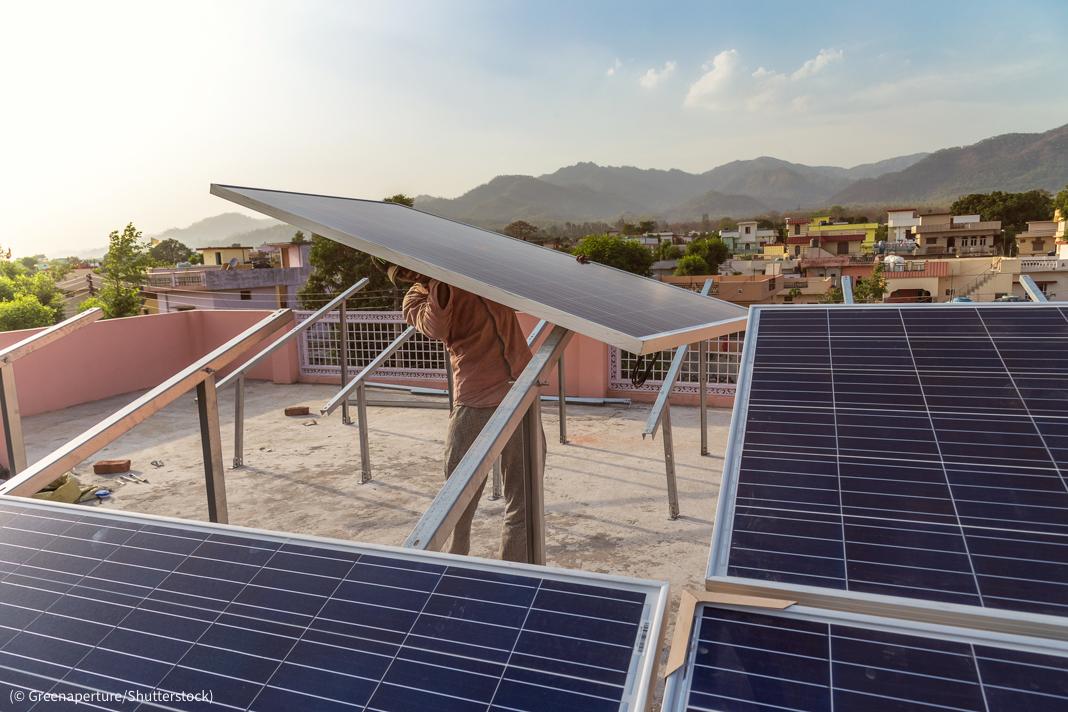 工人站在屋顶上安装太阳能板(© Greenaperture/Shutterstock)