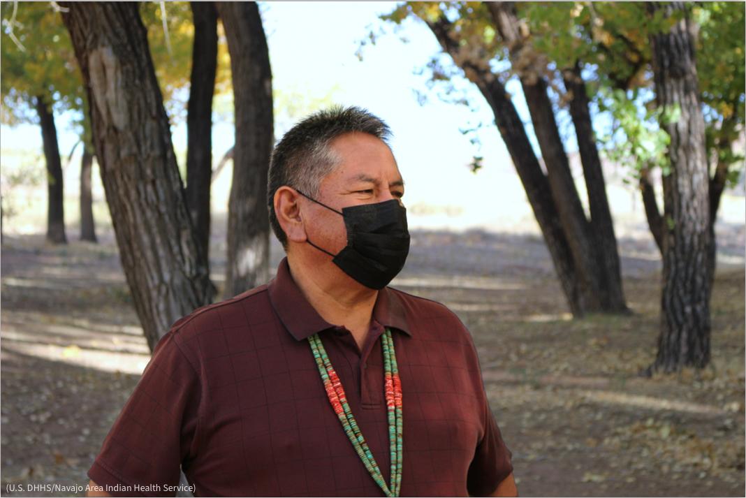 Pria bermasker dengan pepohonan di latar belakang (U.S. DHHS/Navajo Area Indian Health Service)