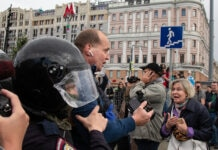 Police escorting man through crowd on city street (© Alexander Zemlianichenko/AP Images)