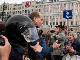 Des policiers escortant un homme à travers une foule massée dans la rue (© Alexander Zemlianichenko/AP Images)