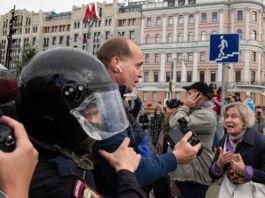 Police escorting man through crowd on city street (© Alexander Zemlianichenko/AP Images)