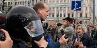 پولیس شہر کی سڑک پر بھیڑ کے بيچ ميں سے ایک شخص کو لے جارہی ہے (© Alexander Zemlianichenko/AP Images)