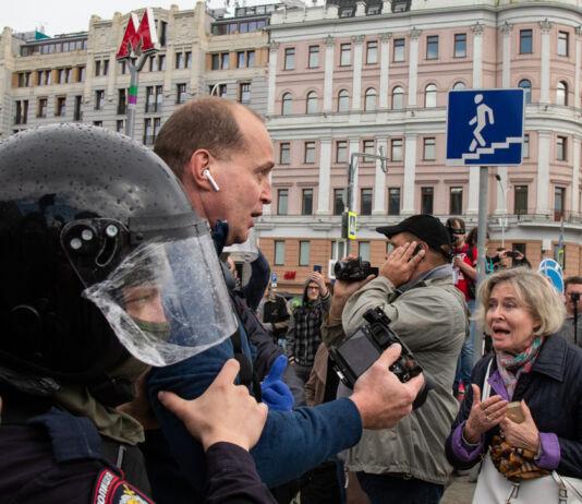 Polisi menggiring seorang pria melewati kerumunan di jalanan kota (© Alexander Zemlianichenko/AP Images)