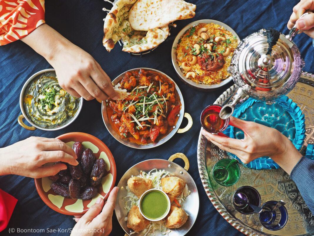 Toutes sortes de plats posés sur une table, et des mains qui se servent (© Boontoom Sae-Kor/Shutterstock)