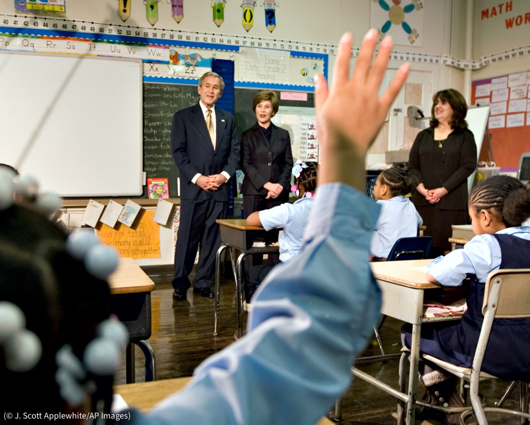 Student in foreground raising hand as George W. Bush and Laura Bush stand in front of classroom (© J. Scott Applewhite/AP Images)