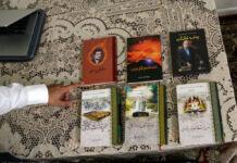 Mano señalando seis libros colocados sobre una mesa (© Jacqueline Larma/AP Images)