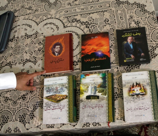 Hand pointing to six books spread out on table (© Jacqueline Larma/AP Images)