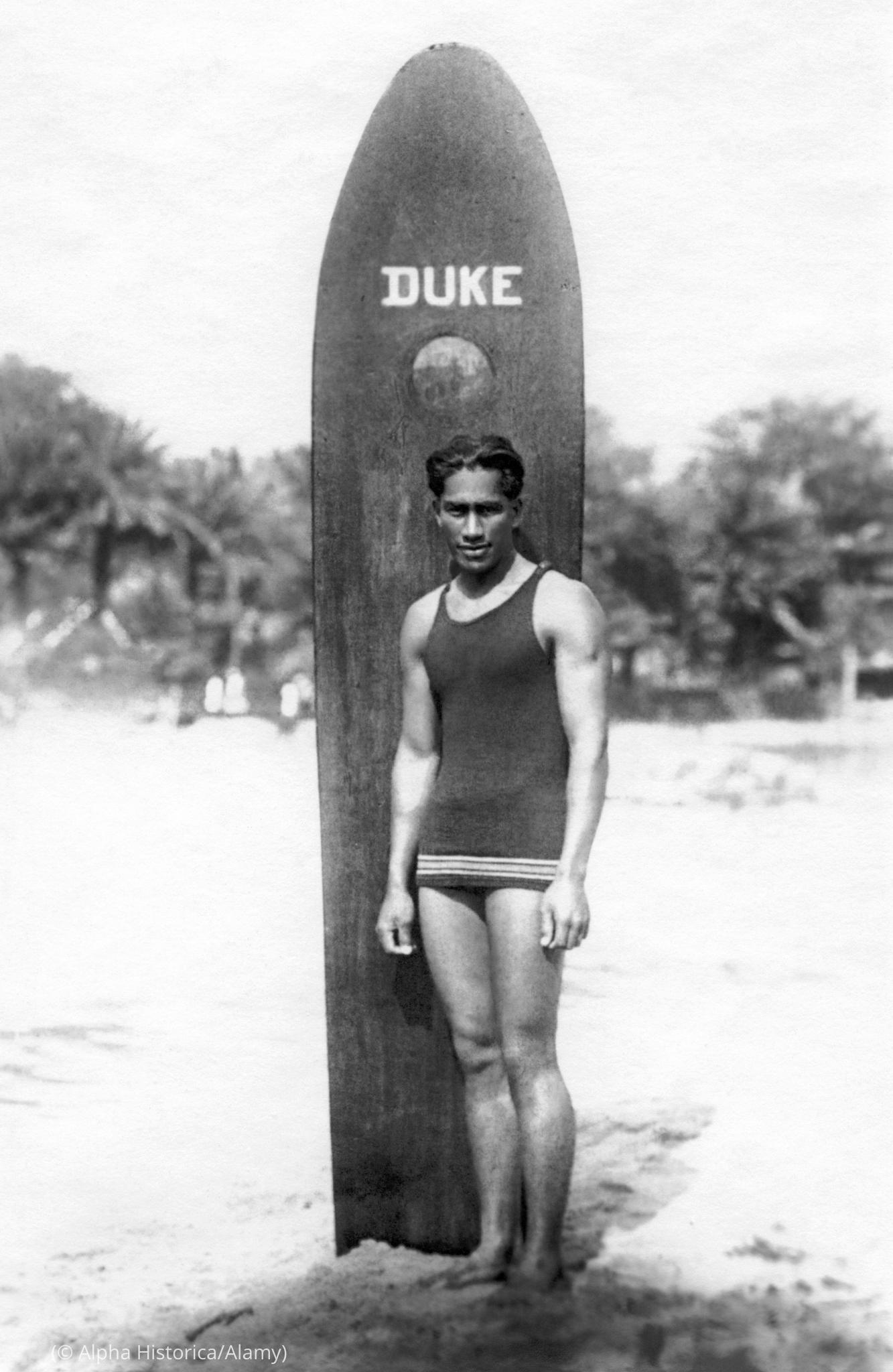 Duke Kahanamoku en traje de baño frente a una tabla de surf en la playa (© Alpha Histórica/Alamy)