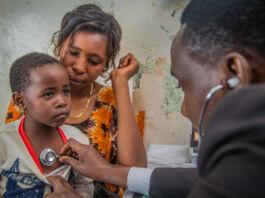 ایک ڈاکٹر سٹیتھو سکوپ کے ذریعے ماں کی گود میں بیٹھے بچے کے دل کی دھڑکن سن رہا ہے (USAID/Riaz Jahanpour)