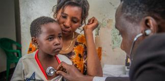 یک پزشک با استتوسکوپ قلب کودکی را که در دامان مادرش نشسته است معاینه می کند. (USAID/Riaz Jahanpour)