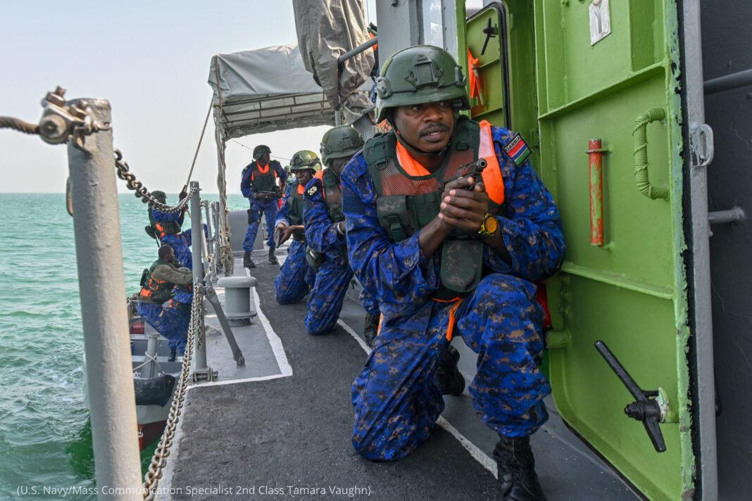Man in military uniform holding gun approaching door on a ship ((U.S. Navy/Mass Communication Specialist 2nd Class Tamara Vaughn)