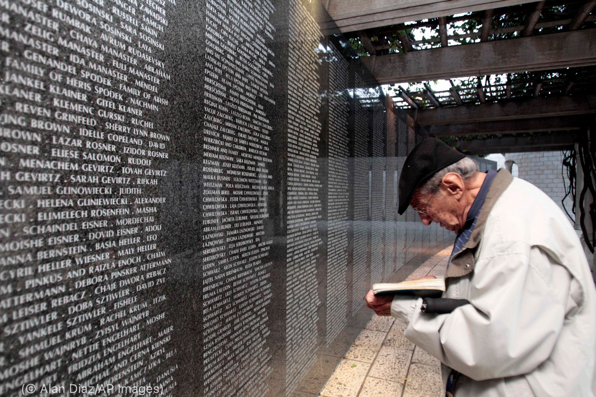 Man holding book and praying beside black granite wall containing many engraved names (© Alan Diaz/AP Images)