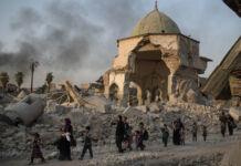 Civilians walking past a heavily damaged mosque and rubble (© Felipe Dana/AP Images)