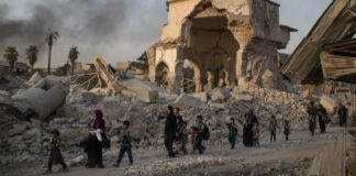 Women and children walking past heavily damaged mosque and rubble (© Felipe Dana/AP Images)