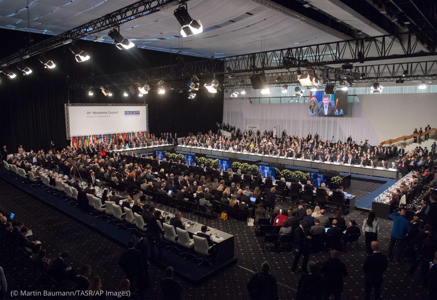 Veľká miestnosť plná ľudí sediacich za dlhými stolmi (© Martin Baumann/TASR/AP Images)