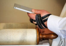 Hand wrapped in leather straps of tefillin holding electronic tablet over Torah (© Jacquelyn Martin/AP Images)