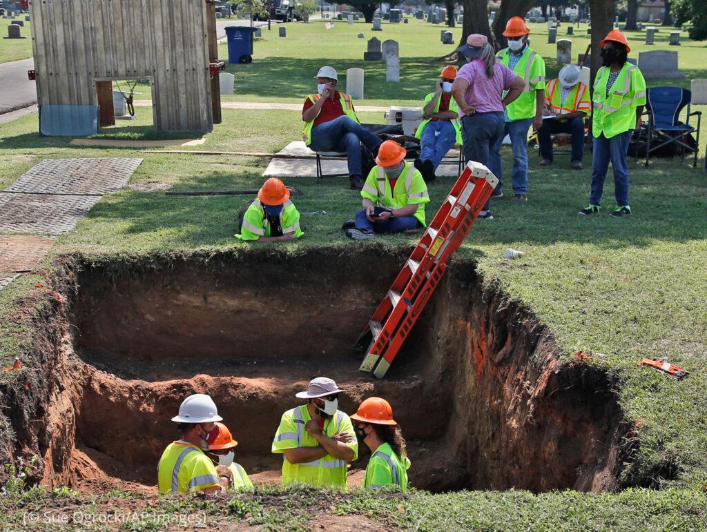 Люди в жилетах работают внутри раскопок на кладбище (© Sue Ogrocki/AP Images)