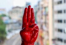 دست پوشیده شده از رنگ که سه انگشت را بالا نگه داشته است . (© AP Images)