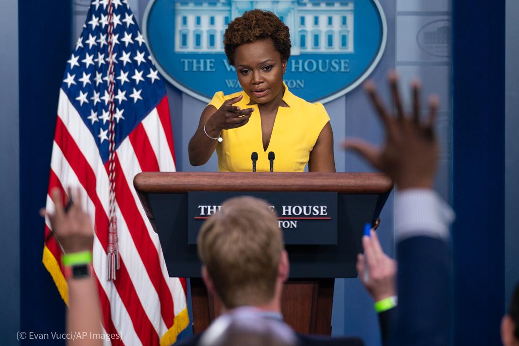 Una mujer habla de pie desde un atril mientras algunas personas levantan la mano para pedir la palabra (© Evan Vucci/AP Images)