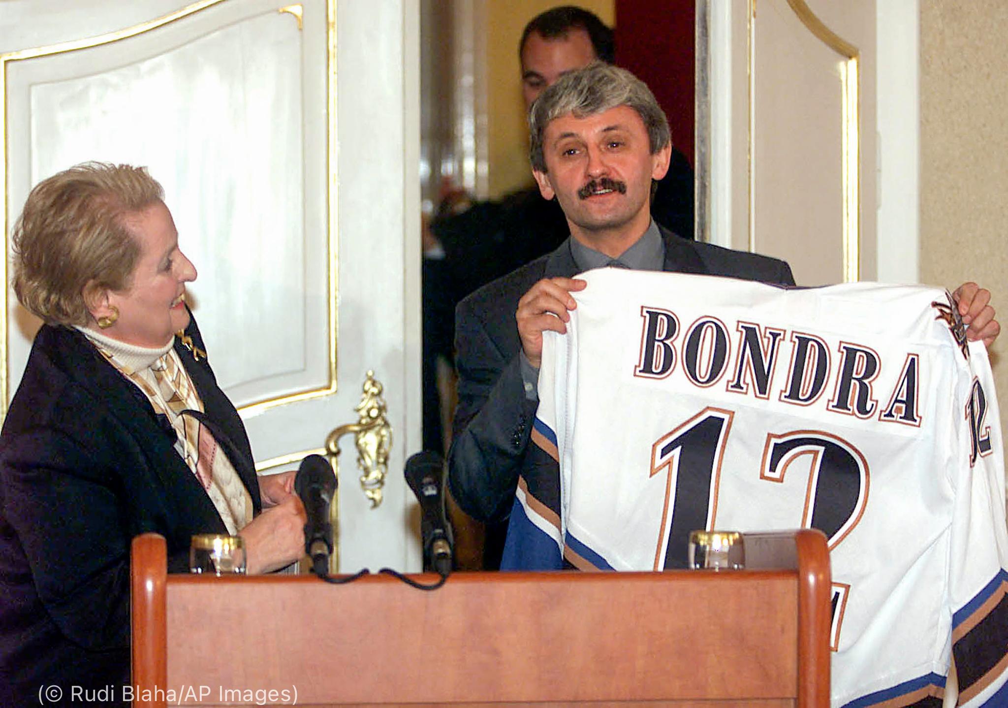 Madeleine Albright looking at Mikuláš Dzurinda holding up hockey jersey (© Rudi Blaha/AP Images)