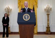 Joe Biden speaking at lectern as Kamala Harris stands behind (© Evan Vucci/AP Images)