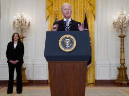 Joe Biden discursa em uma tribuna enquanto Kamala Harris observa em pé atrás (© Evan Vucci/AP Images)