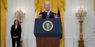 Le président Joe Biden s'exprimant à un pupitre, avec la vice-présidente Kamala Harris debout derrière lui (© Evan Vucci/AP Images)