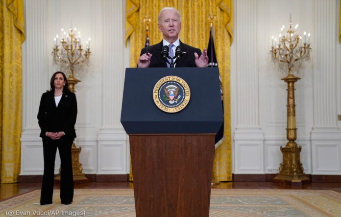 Biden speaking behind a podium as Kamala Harris stands behind (© Evan Vucci/AP Images)