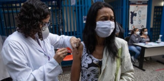 Female health care worker injecting vaccine into to a woman's right arm (© Andre Penner/AP Images)