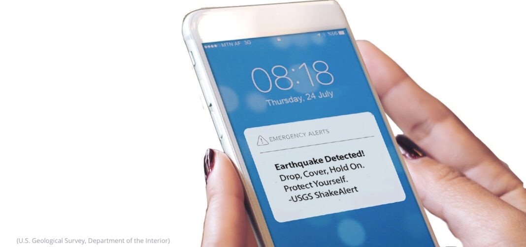 Hand holding a cell phone with a ShakeAlert warning displayed (U.S. Geological Survey, Department of the Interior)