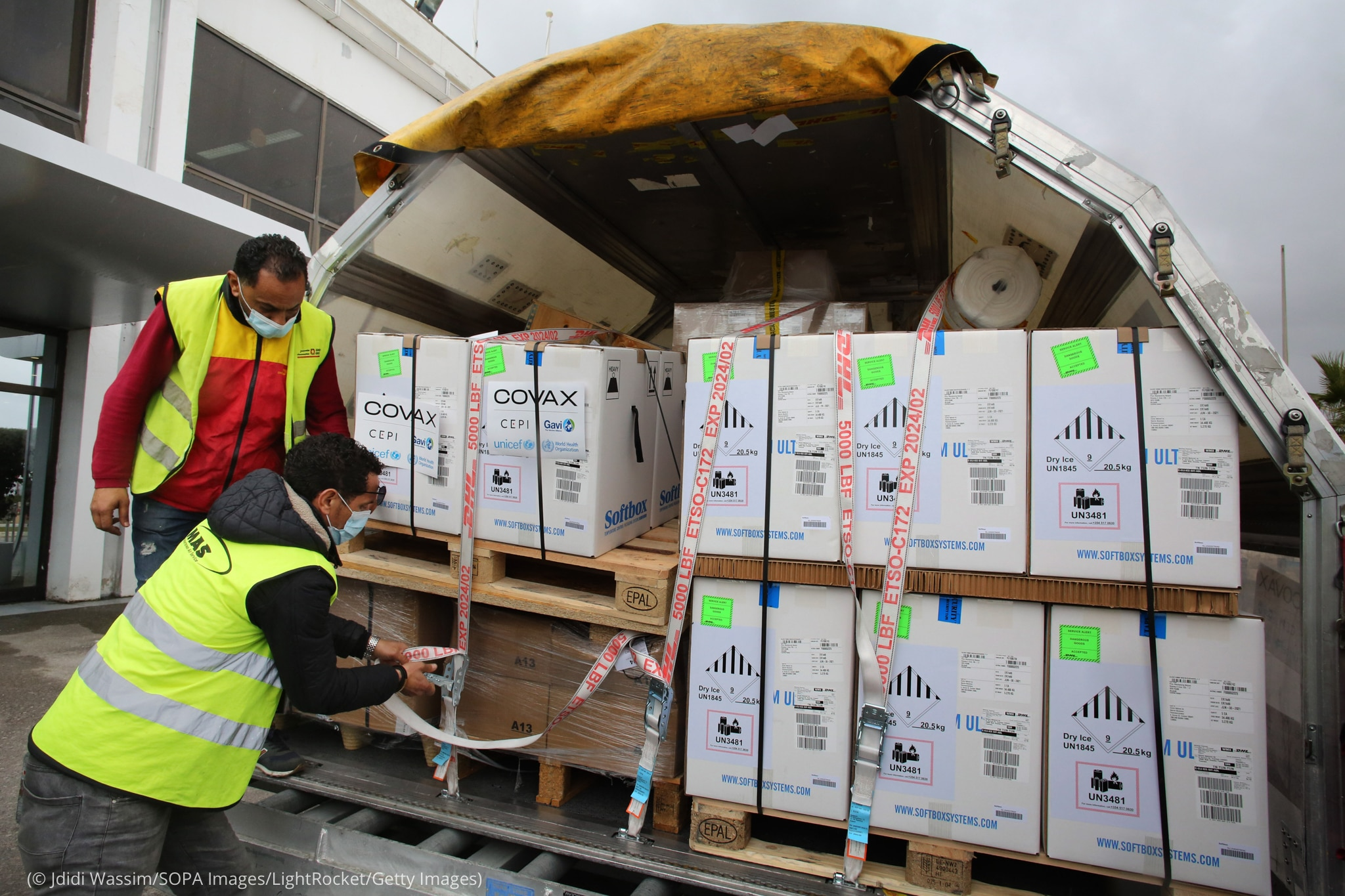 Men unloading boxes of vaccines (© Jdidi Wassim/SOPA Images/LightRocket/Getty Images)
